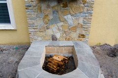 Firepit with quartzite wall and granite cross