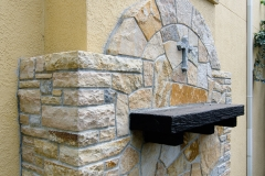 Quartzite wall with granite cross, side view